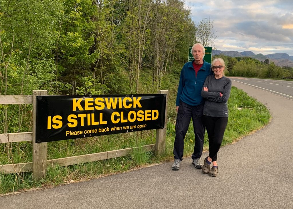 Keswick's mayor Cllr David Burn and his wife Elaine at one of the signs which say 'Keswick is still closed - Please come back when we are open'