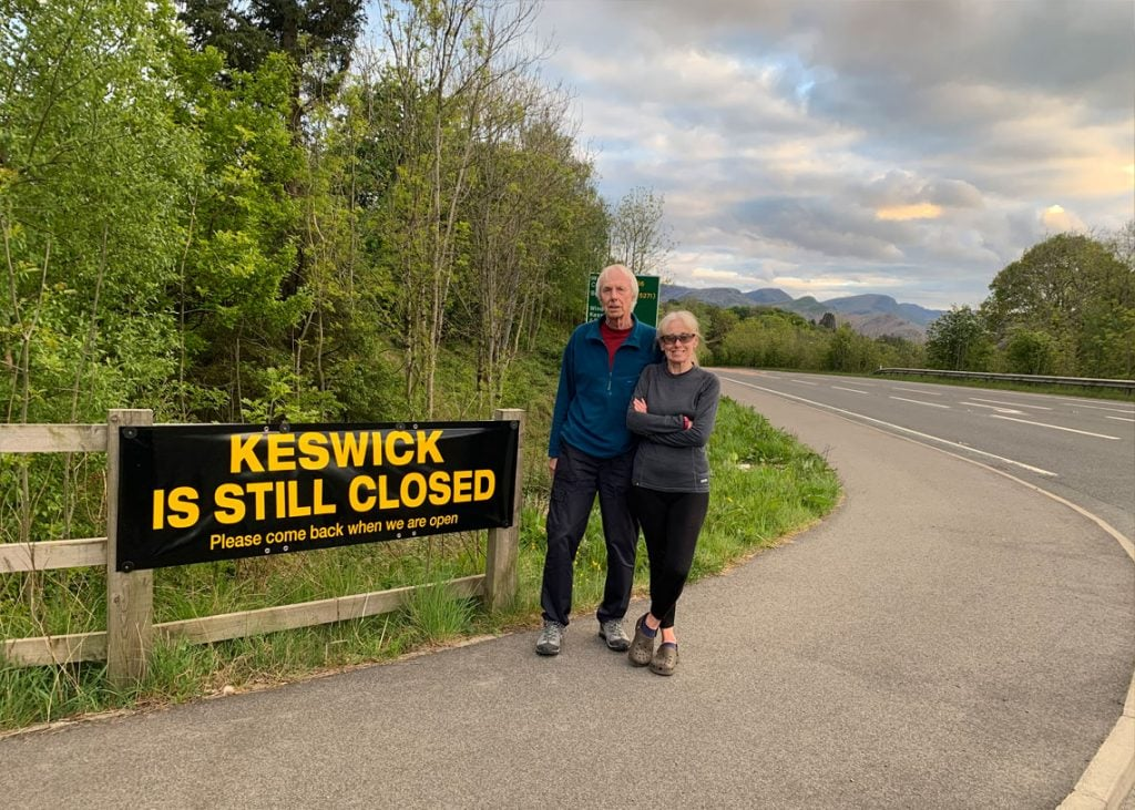 Keswick mayor Cll David Burn and his wife Elaine with one of the signs saying 'Keswick is still closed - Please come back when we are open'